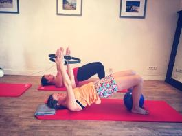 "Training in the CREW Pilates Studio | Esther and Marie achieving an assisted ""pelvic curl"""