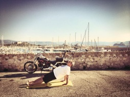 "Outdoor training in Antibes | Captain Chris doing ""back support"" on the mat with his Harley Davidson and super yachts in the background"