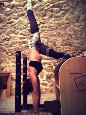 """CREW Pilates owner and instructor Bianca working on """"handstands"""" on the ladder barrel"""